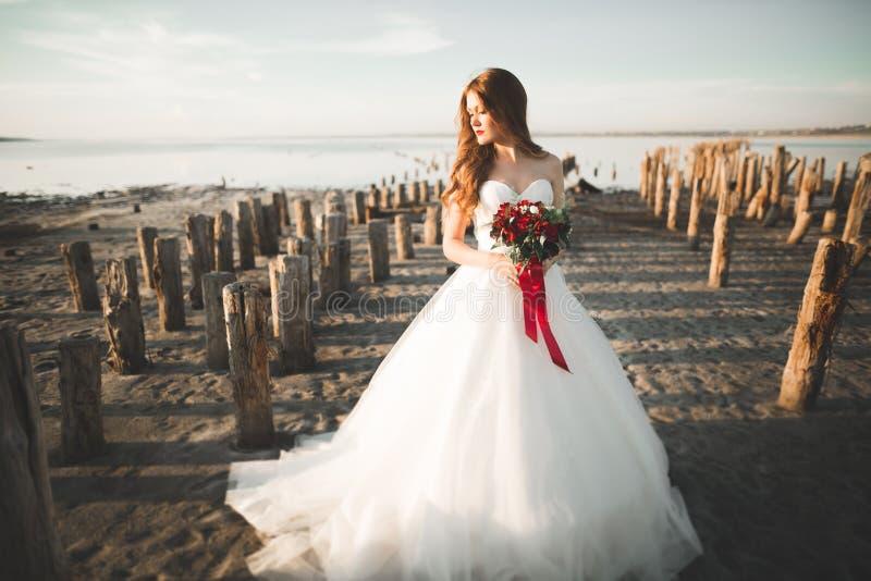 Hübsche Dame, Braut, die in einem Hochzeitskleid nahe Meer auf Sonnenuntergang aufwirft lizenzfreie stockfotos