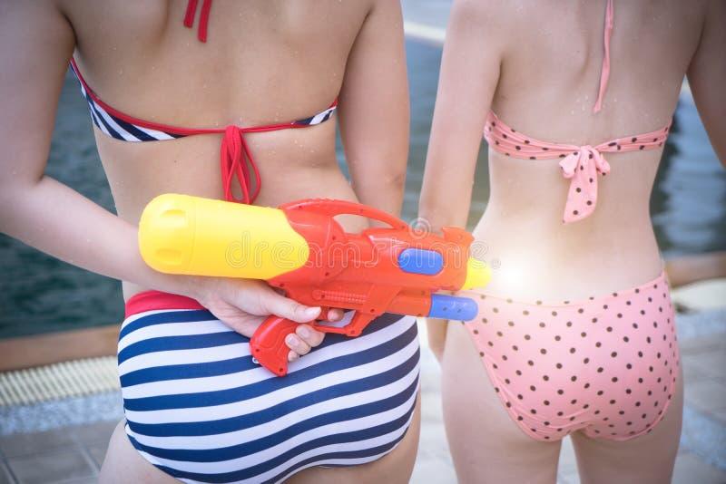 Hübsche Dame, die mit Plastikwasserwerfern spielt, kämpfen an der Poolseite lizenzfreie stockbilder