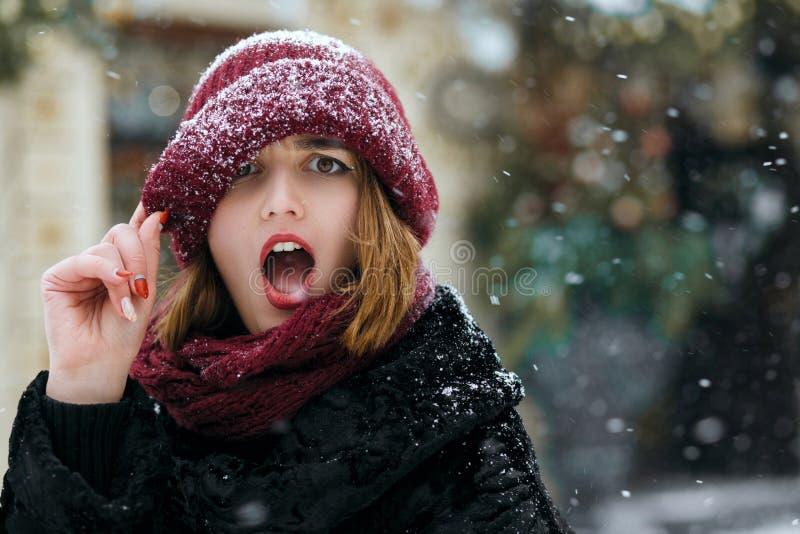 Hübsche emotionale Frau, welche die rote Kappe aufwirft an der Straße während der Schneefälle trägt Raum für Text lizenzfreies stockbild