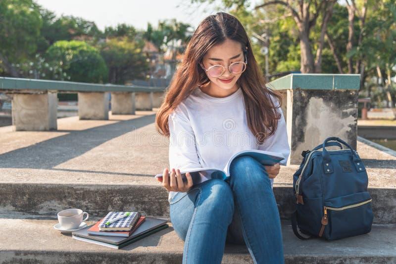 Hübsche entspannte junge Frau, die ein Buch am Rasen mit dem Sonnenglänzen liest stockfoto