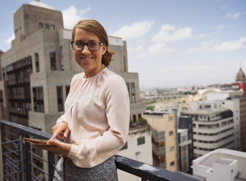 Hübsche Frau auf Balkon mit einer digitalen Tablette lizenzfreie stockfotos