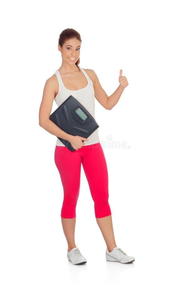 Hübsche Frau auf dem Sehen seiner neuen Gewichtsskala o.k. sagend stockfotografie