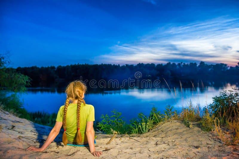 Hübsche Frau auf dem Strand, der Sonnenuntergang betrachtet lizenzfreie stockfotos