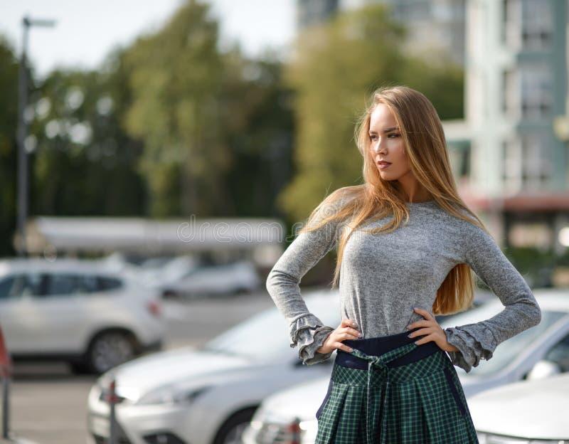 Hübsche Frau auf einer Straße im windigen Haar des Herbstmode-Stoffes stockfoto