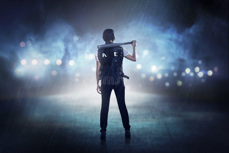 Hübsche Frau in der Polizeiweste, die Baseballschläger hält stockbilder