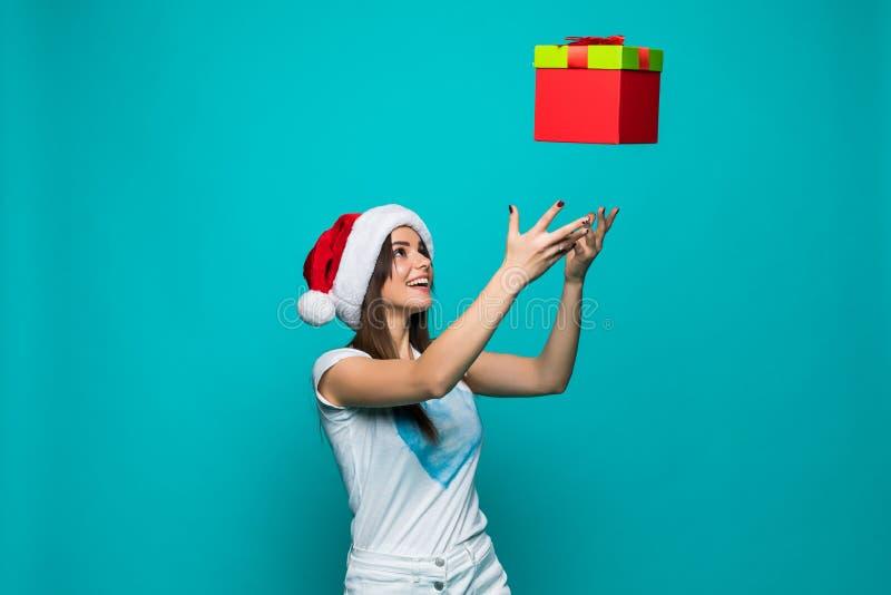 Hübsche Frau der Schönheit in Sankt-Hut fängt mit ihrem Handweihnachtsgeschenk auf Farbhintergrund lizenzfreies stockfoto