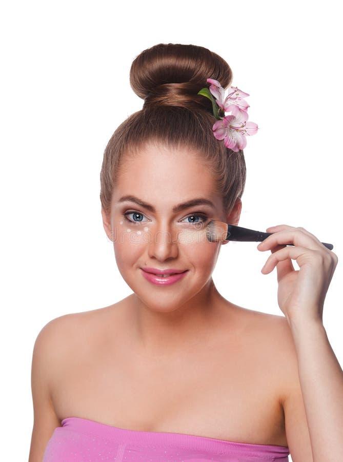 Hübsche Frau, die Abdeckstift mit Bürste anwendet stockbilder