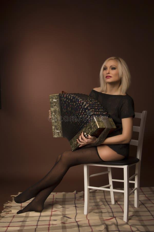 Hübsche Frau, die auf Akkordeon spielt lizenzfreie stockfotos