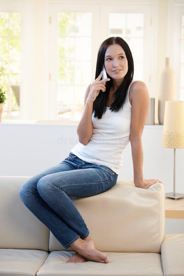 Hübsche Frau, die auf Couch mit Mobiltelefon aufwirft lizenzfreies stockfoto