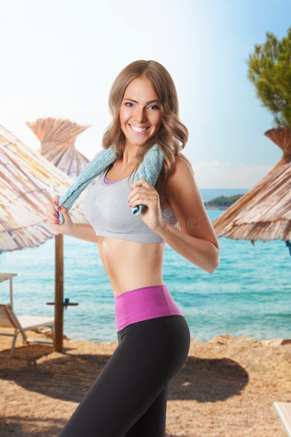 Hübsche Frau, die auf dem Strand ausarbeitet stockbilder