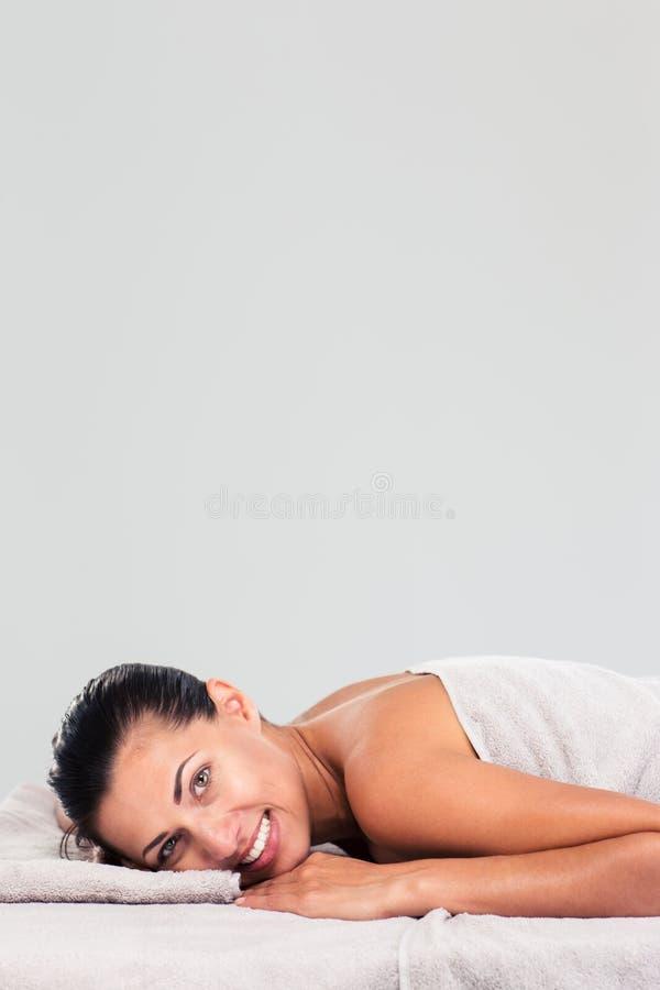 Hübsche Frau, die auf Massageruhesessel liegt lizenzfreie stockfotos