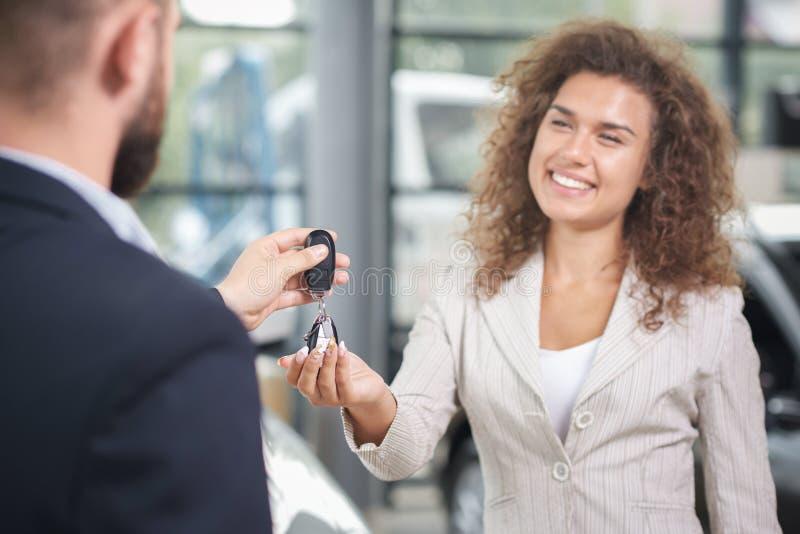 Hübsche Frau, die Autoschlüssel vom Autohändler nimmt lizenzfreie stockfotografie