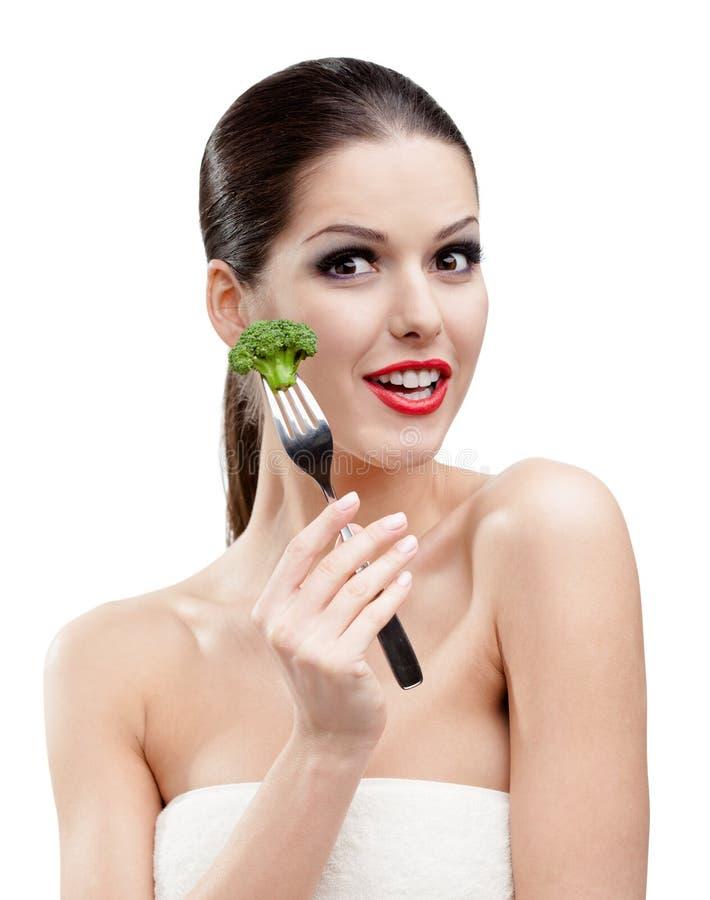 Hübsche Frau, die Brokkoli auf Gabel isst lizenzfreie stockfotografie