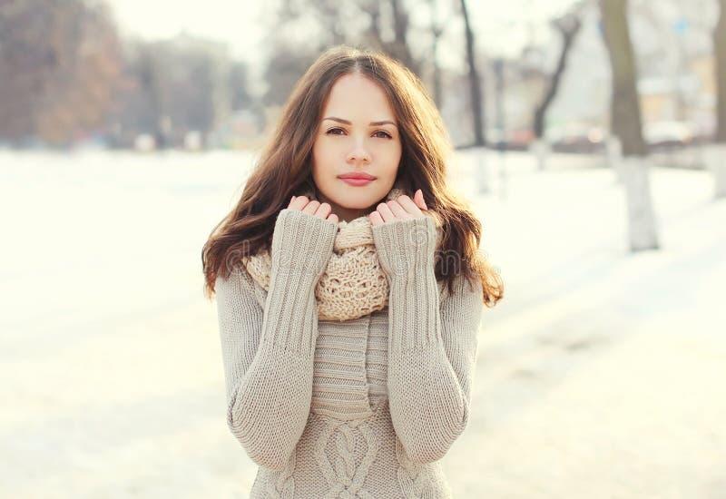 Hübsche Frau, die draußen eine gestrickte Strickjacke und einen Schal im Winter trägt stockfotografie