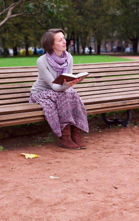 Hübsche Frau, die ein Buch auf Bank und dem Denken liest stockfotografie