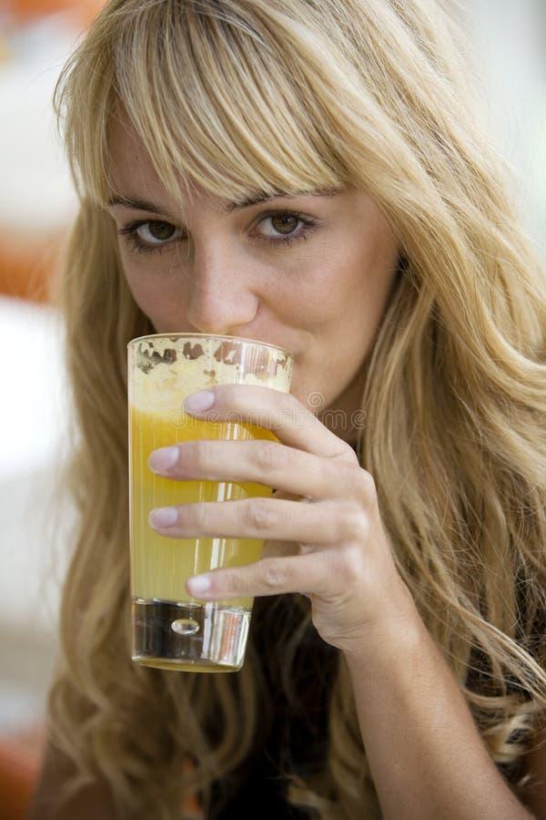 Hübsche Frau, die ein Glas Orangensaft trinkt stockfotografie