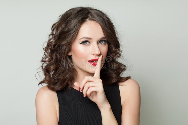 Hübsche Frau, die ein Zeichen der Ruhe zeigt Shh! Die Geheimnisse der Frauen stockfotografie