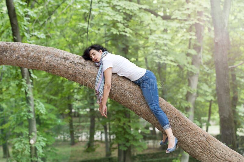 Hübsche Frau, die in einem Baum nachdem Sein über gearbeitet und Haben des Problemschlafens schläft stockbilder