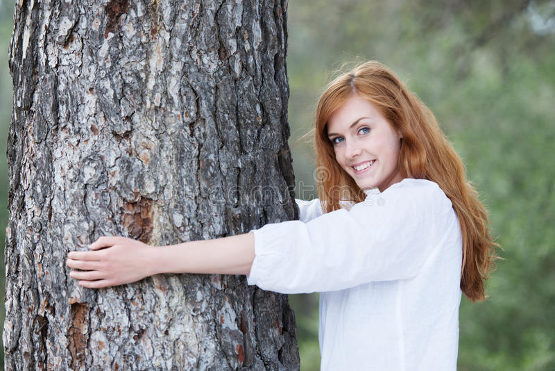 Hübsche Frau, die einen Baum umarmt lizenzfreie stockbilder