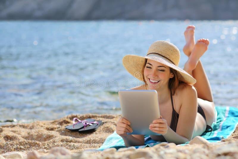 Hübsche Frau, die einen Tablettenleser auf dem Strand auf Ferien liest stockbilder