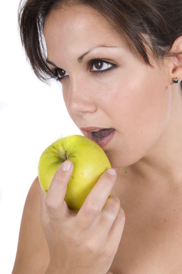 Hübsche Frau, die grünen Apfel isst lizenzfreies stockbild