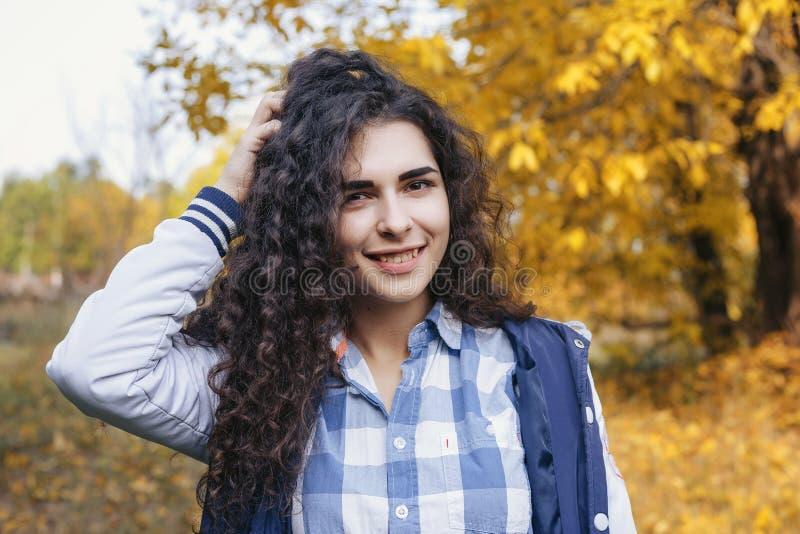 Hübsche Frau, die ihr Haar berührt und an der Kamera lächelt stockfotografie