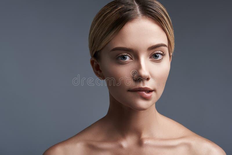 Hübsche Frau, die ihre Lippe beißt und aufmerksam Sie betrachtet stockfoto