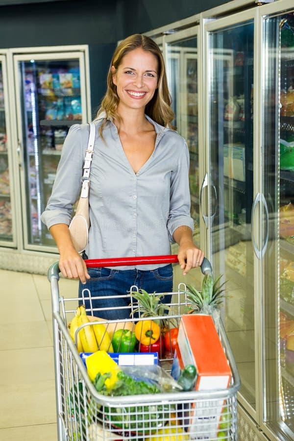 Hübsche Frau, die ihren Einkauf tut lizenzfreie stockfotografie