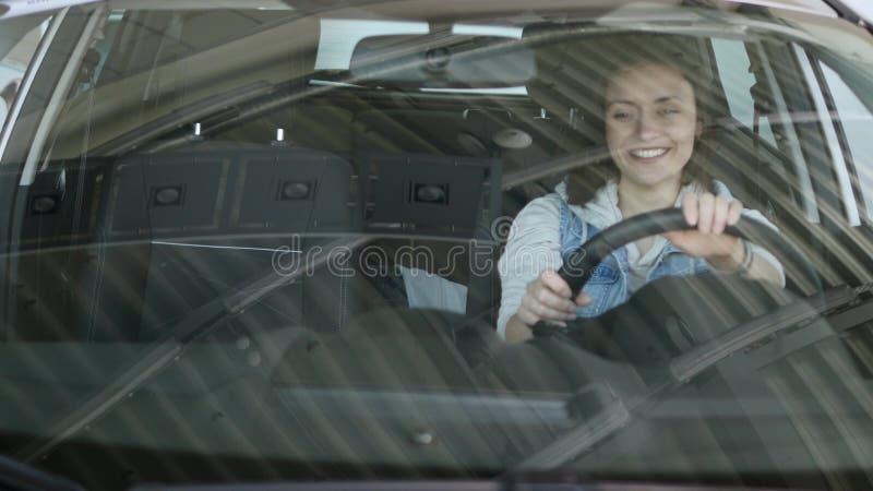 Hübsche Frau, die im Auto sitzt und auf Verkäufer in der Automobilmitte hört Zeitlupen lizenzfreie stockfotos