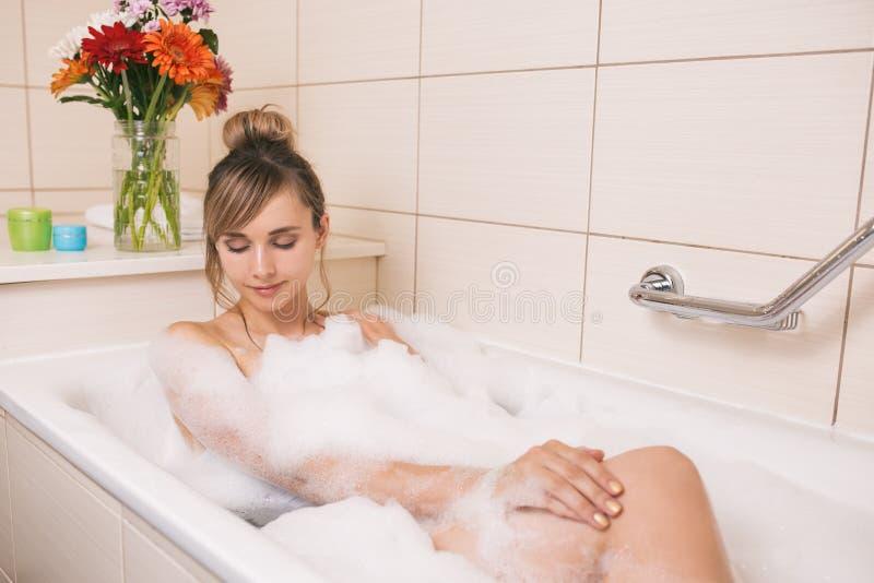 hübsche Frau, die im Badezimmer sich entspannt lizenzfreie stockfotos