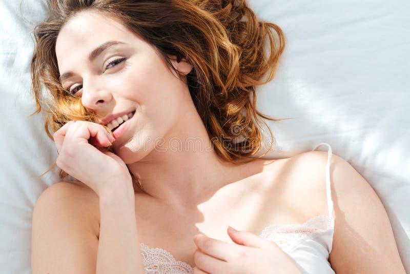Hübsche Frau, die im Bett liegt lizenzfreie stockfotografie