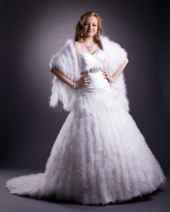 Hübsche Frau, die im luxuriösen Hochzeitskleid aufwirft lizenzfreies stockfoto