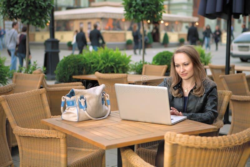 Hübsche Frau, die im Straßenkaffee mit Laptop sitzt stockbild
