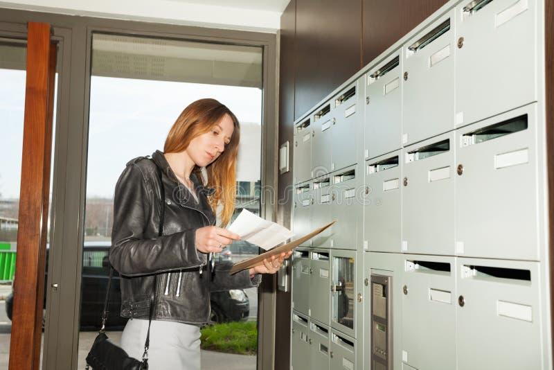 H?bsche Frau, die Junk-Email-Stellung an einer Halle ?berpr?ft stockfotografie