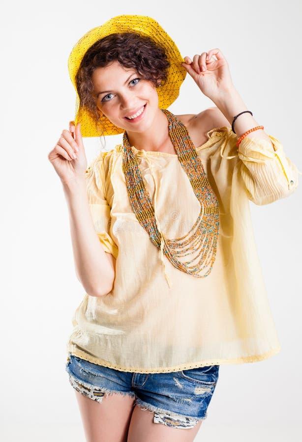 Hübsche Frau, die kurze Jeans und das Sommerhemdlächeln trägt stockfotografie
