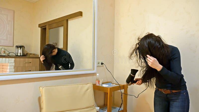 Hübsche Frau, die langes Haar im Make-upraum trocknet lizenzfreie stockbilder