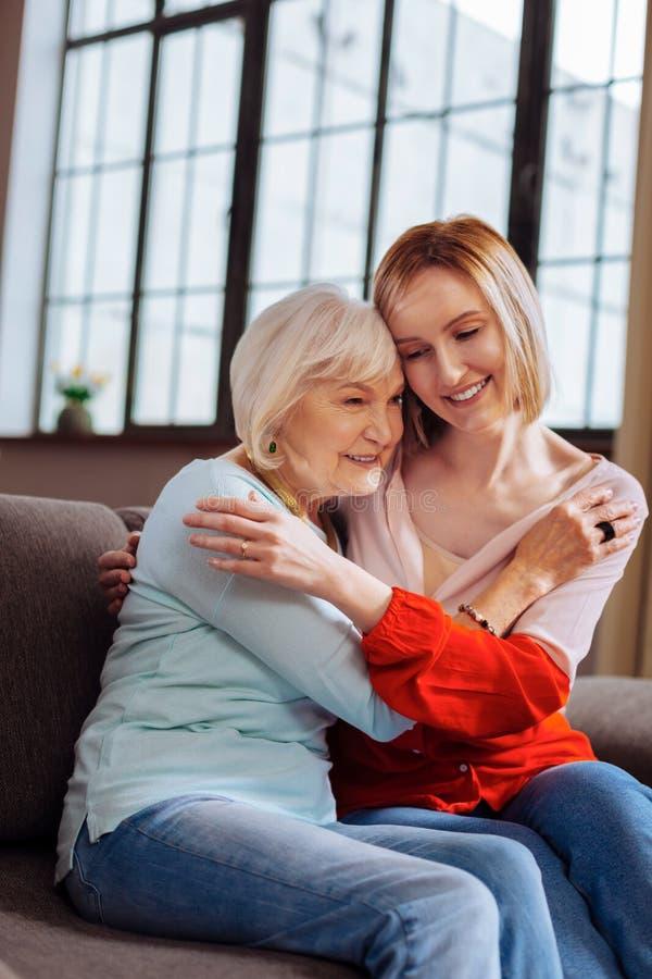 Hübsche Frau, die liebevoll ältere gnädige Frau sitzt auf Couch streichelt lizenzfreie stockfotos