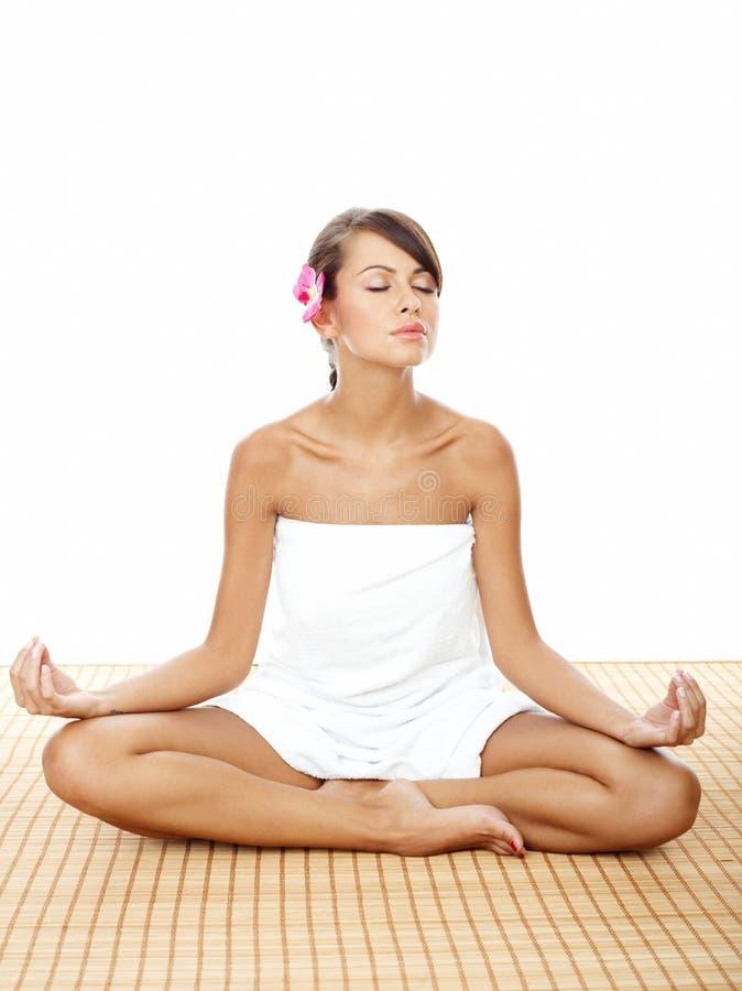 Hübsche Frau, die Lotus Yoga Pose am Badekurort tut lizenzfreie stockfotografie