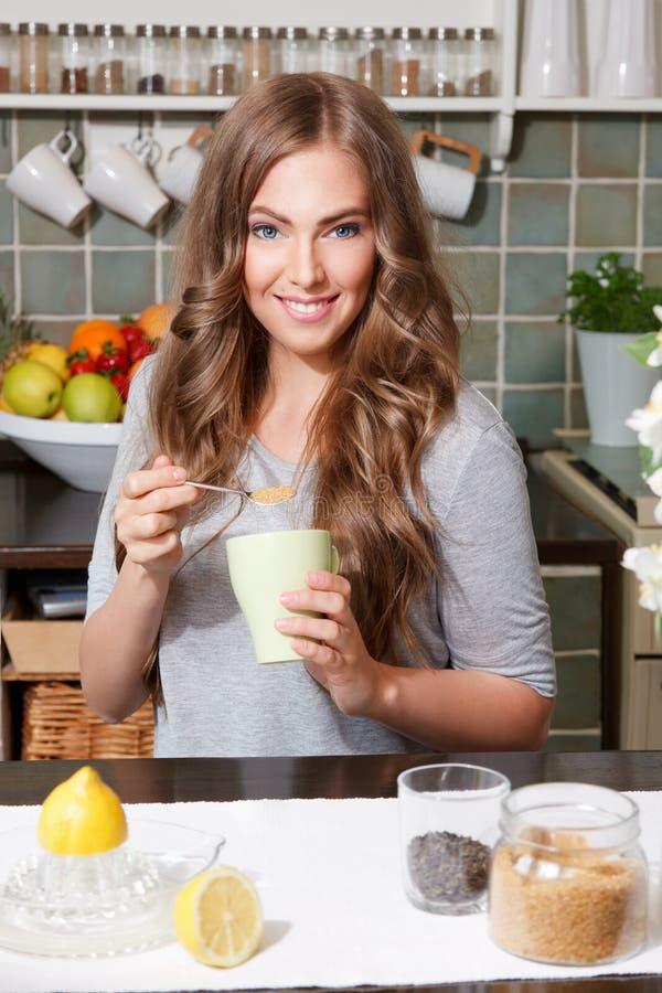 Hübsche Frau, die Rohrzucker Tee hinzufügt lizenzfreie stockfotos