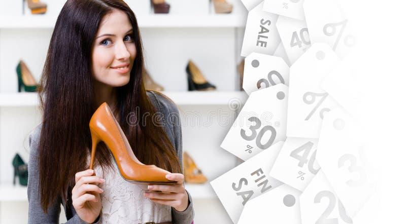 Hübsche Frau, die Stöckelschuh auf Räumungsverkauf hält stockfoto