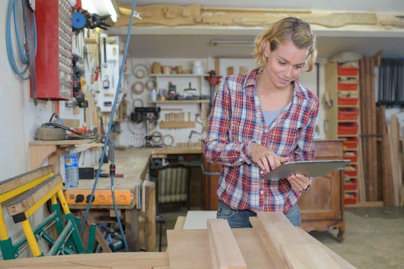 Hübsche Frau, die Tablette in der hölzernen Werkstatt verwendet lizenzfreie stockfotografie