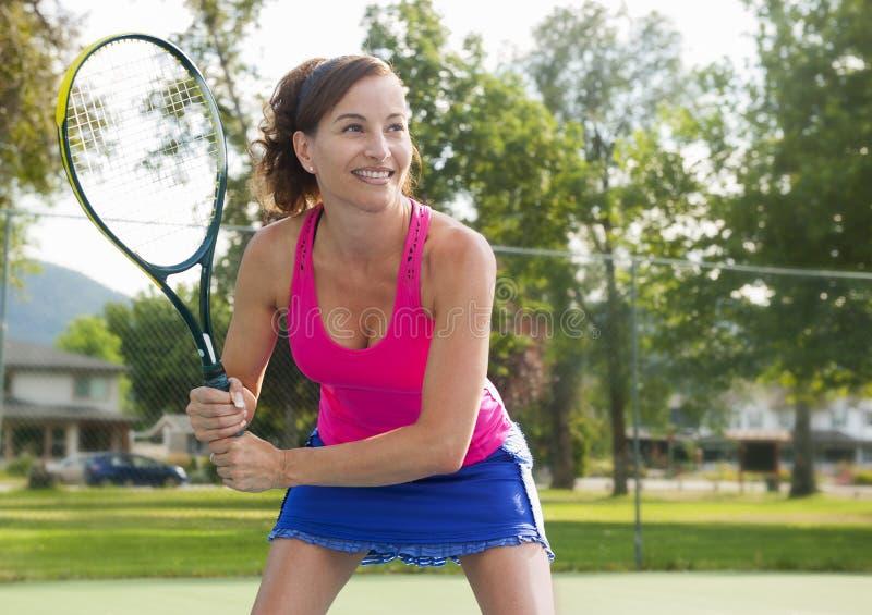Hübsche Frau, die Tennis spielt lizenzfreie stockbilder
