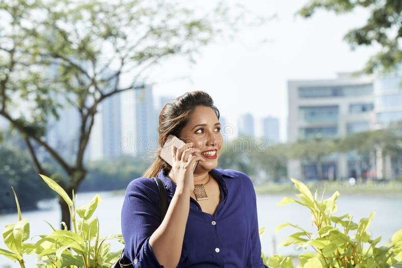 Hübsche Frau, die um Telefon ersucht stockbild
