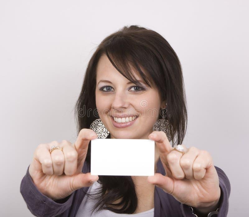 Hübsche Frau, die unbelegte Karte anhält lizenzfreies stockfoto