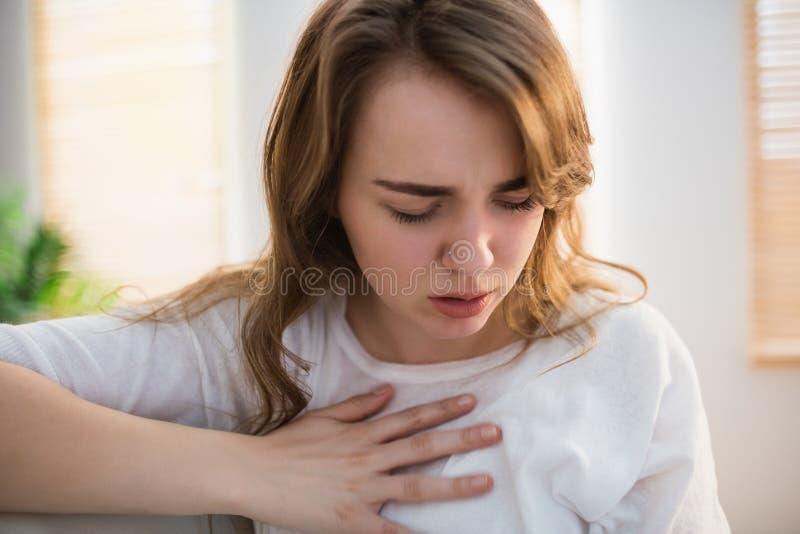 Hübsche Frau, die unter Schmerz in der Brust leidet stockfotos