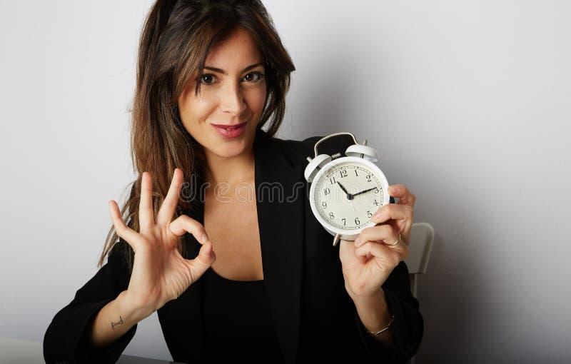 Hübsche Frau, die weißen Weinlesewecker hält und Hand OKAYsymbol über leerem grauem Farbhintergrund zeigt geerntet lizenzfreies stockfoto