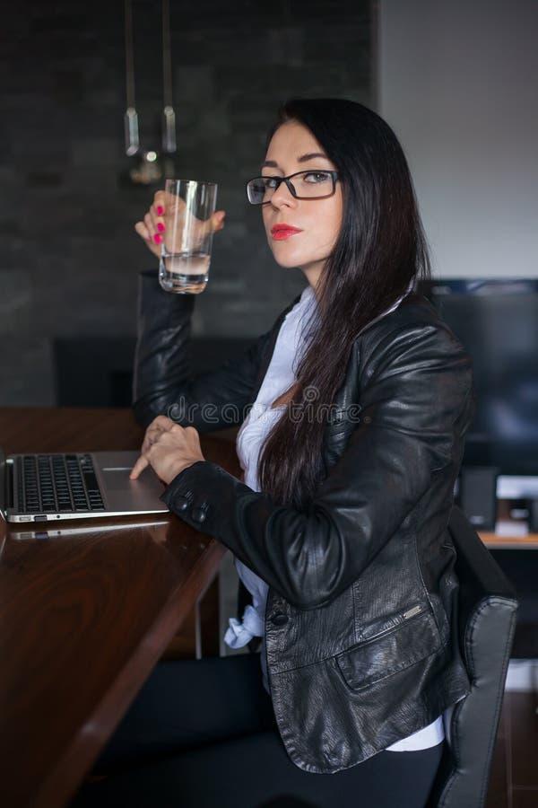 Hübsche Frau, die zu Hause an Laptop arbeitet. lizenzfreies stockfoto