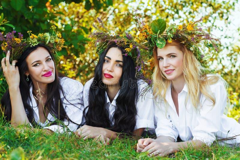 Hübsche Frau drei, die auf dem Gras liegt lizenzfreie stockfotos