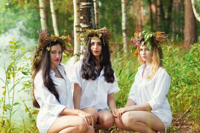Hübsche Frau drei, die im Wald sitzt stockbilder