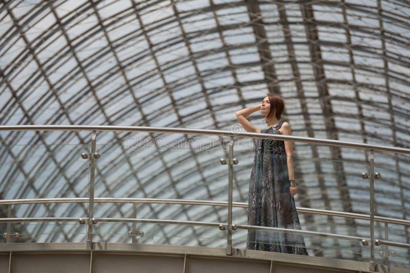 Hübsche Frau in einem modernen Mantel wirft unter dem Dach auf lizenzfreie stockfotos